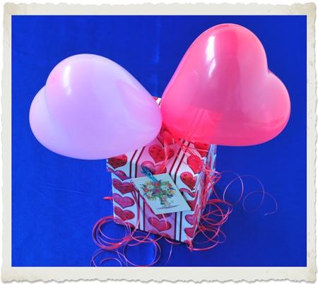 Geschenk mit kleinen Herzluftballons dekoriert